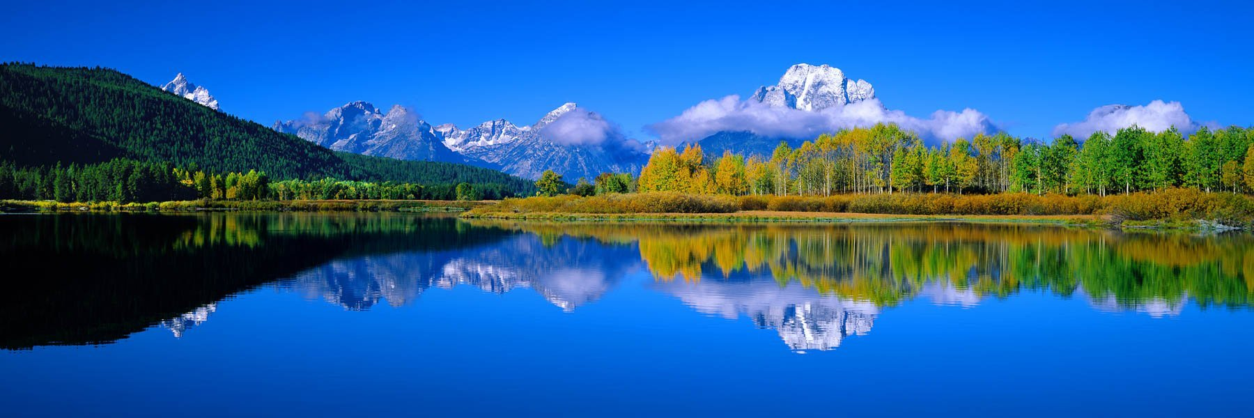 Snow capped peaks of the Grand Tetons, reflected in Snake River, Wyoming, USA.