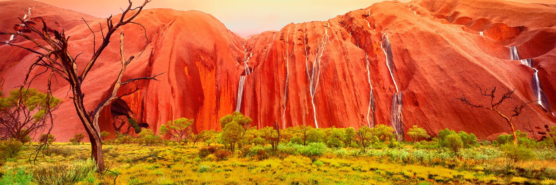 Rain flowing in waterfalls down the sides of Uluru, NT, Australia.