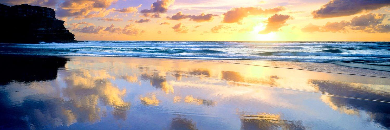 A golden sunrise reflected in wet sand on Avoca Beach, NSW, Australia.