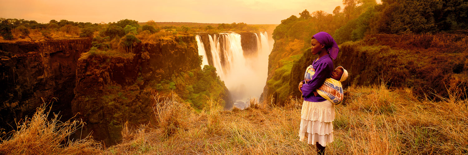 A mother and her child watcing the golden sunset over Vicroria, Falls, Zimbabwe, Africa.