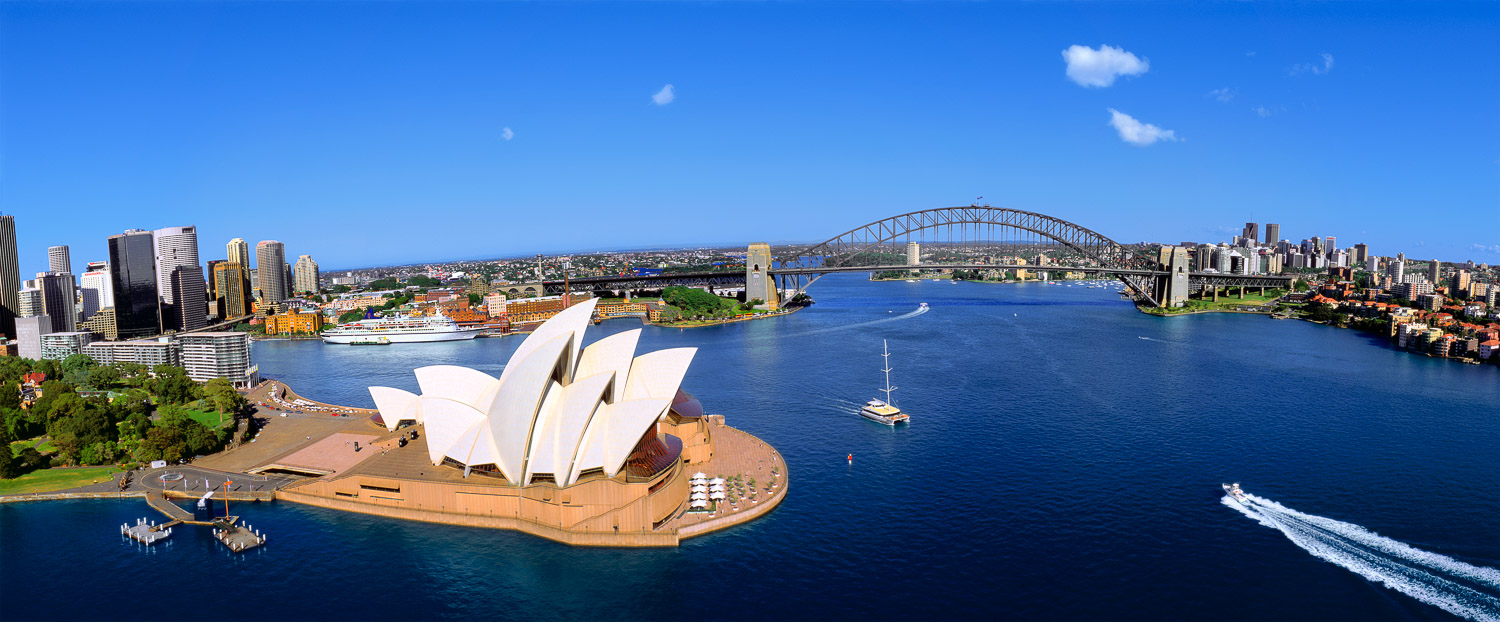 An aerial view of Sydney Harbour, showing bridge and opera house.