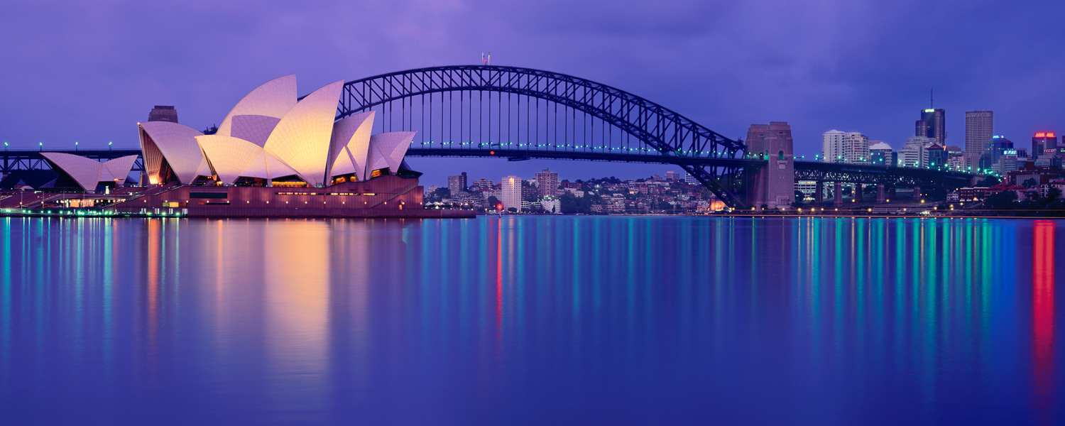 The lights of Sydney Harbour Bridge and Opera House, reflected in the water at sunset, NSW, Australia.